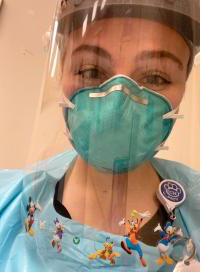 Jennie Kriznik is wearing a mask and a face shield while working as a childlife specialist..